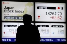 Мужчина у брокерской конторы в Токио. 19 февраля 2015 года. Японский фондовый рынок вырос в пятницу третий день подряд, достигнув 15-летнего максимума, благодаря ослаблению иены и американской статистике. REUTERS/Toru Hanai