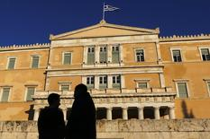 People are silhouetted as they gather ahead of an anti-austerity and pro-government demonstration in front of the parliament in Athens February 20, 2015.   REUTERS/Yannis Behrakis