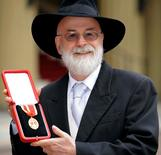 British author Terry Pratchett poses for photographers after receiving his knighthood from Britain's Queen Elizabeth at Buckingham Palace in London February 18, 2009.       REUTERS/Ian Nicholson/Pool