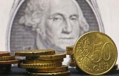 Монеты евро на фоне банкноты в 1 доллар США. Зеница, 13 марта 2015 года. Курс евро к доллару упал до 12-летнего минимума, так как инвесторы вновь принялись продавать евро после недавнего повышения. REUTERS/Dado Ruvic