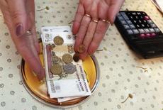 Продавщица выкладывает на прилавок рублевые купюры и монеты в магазине в поселке Верхняя бирюса 23 января 2015 года. Рубль ушел в минус на торгах понедельника за счет смещения баланса сил в сторону покупателей валюты, которые отыгрывают ускорение падения нефтяных цен, тогда как поддержка рублю от продаж экспортной выручки могла сократиться вечером первого дня налогового периода. REUTERS/Ilya Naymushin