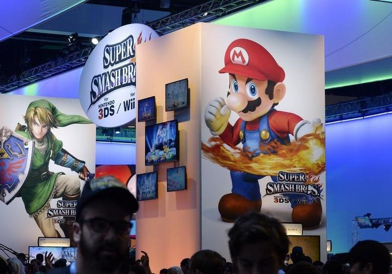 Attendees walk past Nintendo Co.'s Super Smash Bros. signage at the 2014 Electronic Entertainment Expo, known as E3, in Los Angeles, California June 11, 2014.REUTERS/Kevork Djansezian