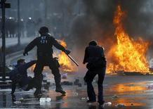 Сотрудник полиции и участники движения Blockupy во время протестов у здания ЕЦБ во Франкфурте-на-Майне 18 марта 2015 года. Противники капитализма схлестнулись с полицией у новой штаб-квартиры Европейского центрального банка (ЕЦБ) во Франкфурте в среду, что сопровождалось поджогами баррикад и автомобилей и омрачило торжественное открытие небоскреба, обошедшегося в миллиард евро. REUTERS/Kai Pfaffenbach