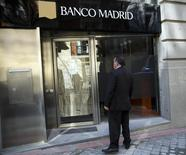 A man stands in front of the entrance of a closed Banco Madrid branch in Madrid, March 16, 2015.  REUTERS/Andrea Comas