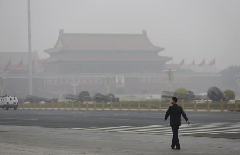 A security personnel walks near Tiananmen Gate on a heavily hazy day in Beijing October 24, 2014.  REUTERS/Jason Lee