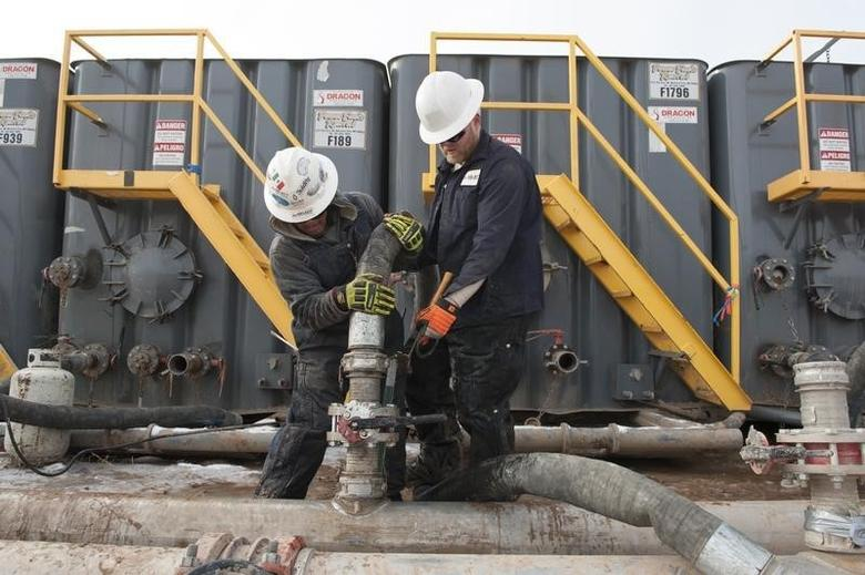 Mody Torres (L) and Josh Anderson of Select Energy Services connect hoses between a pipeline and water tanks at a Hess fracking site near Williston, North Dakota November 12, 2014.REUTERS/Andrew Cullen