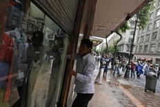Un trabajador cierra una tienda en Ciudad de México, mayo 1 2014. El consumo privado en México creció un 0.5 por ciento entre octubre y diciembre de 2014 frente al trimestre inmediato anterior, dijo el lunes el instituto de estadísticas. REUTERS/Tomas Bravo