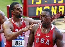 Tyson Gay of the U.S (L) hugs teammate Justin Gatlin (R) after competing in the 4 x 400 m men's event at the Herculis Athletics Meet at Louis II stadium in Monaco July 20, 2012. USA won the race.      REUTERS/Eric Gaillard