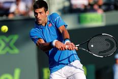 Novak Djokovic hits a backhand against Steve Darcis (not pictured) on day eight of the Miami Open at Crandon Park Tennis Center. Djokovic won 6-0, 7-5. Mandatory Credit: Geoff Burke-USA TODAY Sports