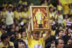 Мальчик держит портрет короля Таиланда Пхумипона Адульядета в Бангкоке. 5 декабря 2014 года. Тайский военный суд приговорил во вторник мужчину к 25 годам тюрьмы за размещение изображений на его странице Facebook, которые были признаны оскорбляющими местную королевскую семью. REUTERS/Athit Perawongmetha