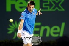 Apr 2, 2015; Key Biscayne, FL, USA; Novak Djokovic hits a backhand against David Ferrer (not pictured) in a men's singles quarter-final on day eleven of the Miami Open at Crandon Park Tennis Center. Djokovic won 7-5, 7-5. Mandatory Credit: Geoff Burke-USA TODAY Sports