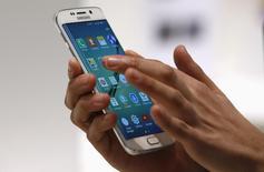 Samsung Electronics a probablement subi une nouvelle baisse de ses bénéfices durant le trimestre janvier-mars, la sixième d'affilée, mais les investisseurs pensent que le géant sud-coréen redressera la barre cette année grâce à ses nouveaux smartphones, comme le Galaxy S6 Edge (photo), et à de solides ventes de semiconducteurs. /Photo prise le 2 mars 2015/REUTERS/Gustau Nacarino
