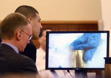Former New England Patriots tight end Aaron Hernandez with attorney Charles Rankin view an image of the bubble gum and the bullet shell on the screen during his murder trial at Bristol County Superior Court in Fall River, Massachusetts, April 6, 2015.  REUTERS/Ted Fitzgerald/Pool