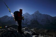 A trekker stands in front of Mount Everest, which is 8,850 meters high (C), at Kala Patthar in Solukhumbu District in this May 7, 2014 file photo.  REUTERS/Navesh Chitrakar