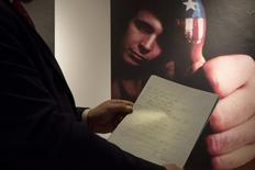 "Christie's curator Tom Lecky holds the original manuscript for singer Don McLean's ""American Pie"" at Christie's auction house in New York April 2, 2015.   REUTERS/Brendan McDermid"