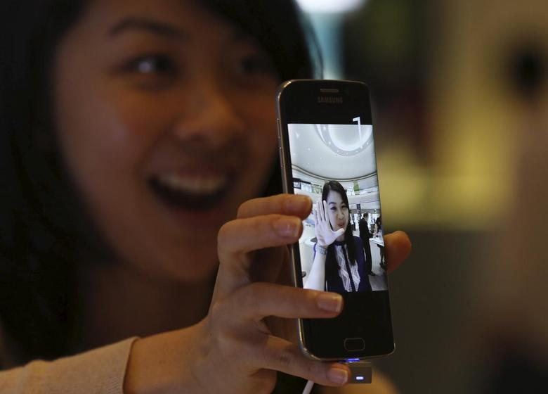 A woman uses the camera on a Samsung Galaxy S6 phone during a pre-launch event in Singapore April 10, 2015.  REUTERS/Edgar Su