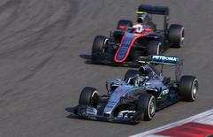 Mercedes Formula One driver Nico Rosberg (front) of Germany drives in front of McLaren Formula One driver Jenson Button of Britain during the Chinese F1 Grand Prix at the Shanghai International Circuit, April 12, 2015. REUTERS/Aly Song