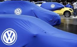 A man unveils a Volkswagen car during the International Sao Paulo Motor Show media day in Sao Paulo October 28, 2014. REUTERS/Paulo Whitaker (BRAZIL - Tags: TRANSPORT BUSINESS LOGO)