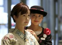 A reception employee of Nihonbashi Mitsukoshi department store (R) poses for a photo with a kimono-clad android robot named Aiko Chihira, developed by Toshiba Corp., during its unveiling at the reception desk of the store in Tokyo April 20, 2015.  REUTERS/Issei Kato