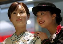 Uma atendente da loja de departamento japonesa Nihonbashi Mitsukoshi posa ao lado do robô humanoide Aiko Chihira, desenvolvido pela Toshiba, em Tóquio  20/042015.  REUTERS/Issei Kato