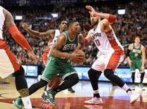 Boston Celtics guard Marcus Smart (36) drives into the key against Toronto Raptors center Jonas Valanciunas (17) and guard Lou Williams (23 )in the second half at Air Canada Centre. Apr 4, 2015; Toronto, Ontario, CAN;  Dan Hamilton-USA TODAY Sports