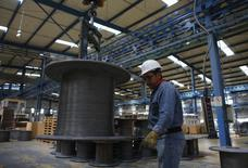 Un trabajador sostiene un cable de acero inoxidable en la planta de TIM en Huamantla, México, oct 11 2013. La actividad económica de México se mantuvo estable en febrero, en medio de una caída en el sector agrícola que fue contenida por un avance de la industria y un magro desempeño de los servicios. REUTERS/Tomas Bravo