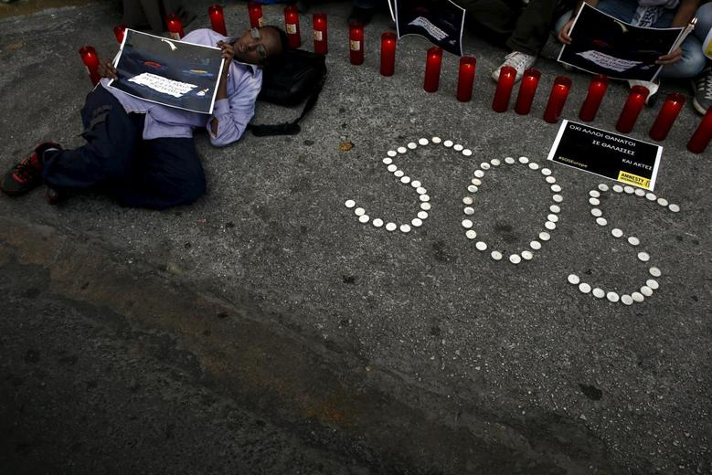 An immigrant holding a placard that reads '' Sleep quiet  we will not come we got dr?wn'' lies on the street during a protest to raise awareness for the deaths of immigrants in the Mediterranean, outside the European Commission office in Athens, April 22, 2015. REUTERS/Kostas Tsironis