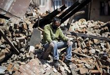 Мужчина сидит на обломках здания, разрушенного землетрясением. Бхактапур, Непал, 27 апреля 2015 года. Сотни непальцев, разозленных и ошарашенных медленной реакцией властей, пытаются сами добраться до близких, погребенных под обломками зданий, уничтоженных мощнейшим землетрясением, которое унесло жизни более 4.000 человек. REUTERS/Adnan Abidi