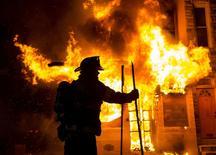 Пожарный тушит огонь в магазине и жилом доме в Балтиморе. 28 апреля 2015 года. Власти объявили в Балтиморе чрезвычайное положение и отправили национальных гвардейцев в американский город, значительную часть которого охватили беспорядки после похорон 25-летнего чернокожего, умершего от травмы позвоночника после задержания полицией. REUTERS/Eric Thayer