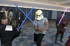 Star Wars: The Force Awakens cast member John Boyega disguises his identity with a helmet and engages unknowing fans in a light saber fight scene at the Star Wars Celebration convention in Anaheim, California, April 16, 2015.   REUTERS/David McNew