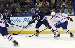 May 6, 2015; Tampa, FL, USA; Tampa Bay Lightning center Tyler Johnson (9) passes the puck as Montreal Canadiens defenseman Tom Gilbert (77) defends during the second period of game three of the second round of the 2015 Stanley Cup Playoffs at Amalie Arena. Mandatory Credit: Kim Klement-USA TODAY Sports