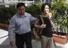 Amos Yee eats a banana as he arrives with his father to the State Courts for a pre-trial conference in Singapore April 17, 2015. REUTERS/Edgar Su