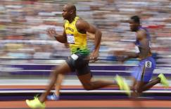 Asafa Powell of Jamaica runs on his way to winning his 100m heat round 1 during the London 2012 Olympic Games at the Olympic Stadium August 4, 2012.     REUTERS/Phil Noble