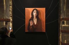Visitante tira foto de obra da artista síria Sara Shamma em exibição em Damasco. 11/01/2011 REUTERS/Khaled Al-Hariri