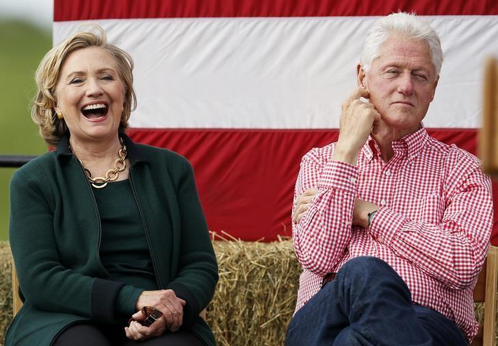 Former U.S. Secretary of State Hillary Clinton (L) and her husband former U.S. President Bill Clinton listen to remarks at the 37th Harkin Steak Fry in Indianola, Iowa, September 14, 2014. REUTERS/Jim Young