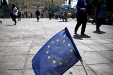 People make their way past a small European Union flag on Constitution (Syntagma) Square, with the parliament building seen in the background, in Athens May 11, 2015.  REUTERS/Alkis Konstantinidis