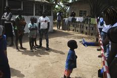 Trabalhadores sociais medindo temperatura de menino que esteve em contato com o vírus do Ebola, na Libéria.   21/01/2015   REUTERS/James Giahyue