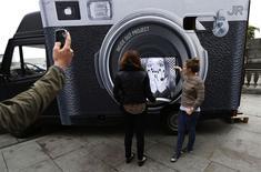 """Una mujer mira su foto, que acaba de imprimirse, para el proyecto """"Acciones"""" en la terraza de Somerset House en Londres el 7 de octubre de 2013. Londres abrirá esta semana una gran feria de fotografía, en su competición con París por atraer a comerciantes, coleccionistas y aficionados. REUTERS/Suzanne Plunkett"""