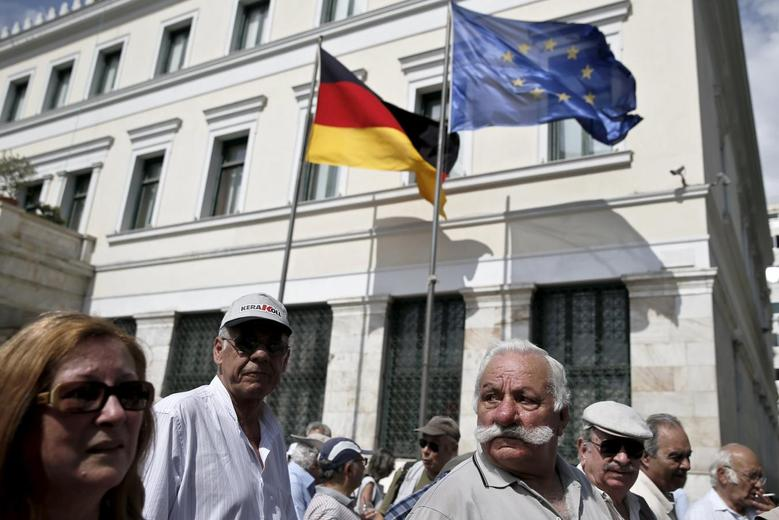 Greek pensioners take part in a demonstration for better healthcare as a European Union flag and a German national flag flutter on the Athens' municipality building, on the occasion of the announcement of a common Greek-German art festival, in Athens May 20, 2015. REUTERS/Alkis Konstantinidis