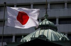 Una bandera japonesa ondea sobre el edificio del Banco de Japón, en Tokyo, 22 de mayo de 2015. El Banco de Japón mantuvo el viernes su programa de estímulo y ofreció una visión ligeramente más optimista de la tercera mayor economía del mundo, citando un modesto repunte en el consumo y las exportaciones. REUTERS/Toru Hanai