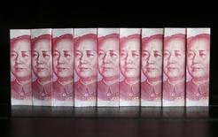 Ilustración fotográfica realizada en Pekín de unos billetes de 100 yuan, jul 11 2013. El Banco Central de Chile dijo el lunes que firmó un acuerdo con su homólogo de la República Popular China por un swap cambiario por hasta 22.000 millones de yuanes (3.600 millones de dólares) para alentar el comercio entre ambos países. REUTERS/Jason Lee