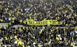 """Supporters of Beitar Jerusalem soccer club hold a banner reading """"Beitar will always remain pure"""" during a Premier League match in Jerusalem January 26, 2013.  REUTERS/Stringer"""