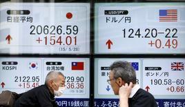 Peatones caminan junto a un tablero electrónico que muestra el índice Nikkei de Japón (arriba a la izquierda), y la tasa cambiaria entre el yen japonés y el dólar estadounidense (arriba a la derecha), afuera de una agencia de la bolsa, en Tokyo, Japón, 28 de mayo de 2015. El dólar subió el martes a un nuevo máximo en 12 años y medio contra el yen, y las bolsas de Asia caían por segundo día consecutivo en momentos en que el fortalecimiento del dólar presionaba a los precios de las materias primas. REUTERS/Yuya Shino