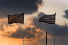 A European Union flag flatters next to a Greek flag atop the Greek Ministry of Finance during sunset in central Athens, Greece June 5, 2015. REUTERS/Yannis Behrakis