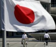 Trabalhadores atrás da bandeira nacional japonesa vista em Tóquio.  21/05/2015     REUTERS/Toru Hanai