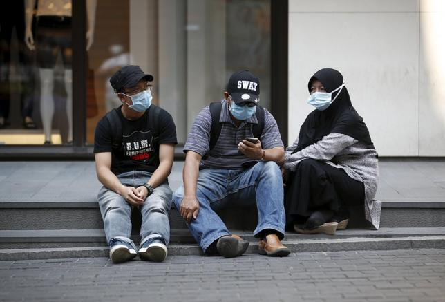 Tourists wearing masks to prevent contracting Middle East Respiratory Syndrome (MERS) rest at Myeongdong shopping district in central Seoul, South Korea, June 12, 2015. REUTERS/Kim Hong-Ji
