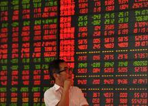 Инвестор в брокерской конторе в Фуяне. 12 июня 2015 года. Азиатские фондовые рынки снизились в понедельник из-за провала переговоров Греции с кредиторами и накануне совещания ФРС. REUTERS/China Daily