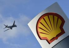 A passenger plane flies over a Shell logo at a petrol station in west London, January 29, 2015.   REUTERS/Toby Melville