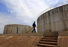 Сотрудник Canadian Pacific Rubiales Petroleum Company у емкостей с нефтью в Мете, Колумбия 11 февраля 2015 года. Избыток нефти на мировом рынке, ставший одной из причин начавшегося год назад резкого падения цен, сохраняется, и аналитики считают, что он может только вырасти. REUTERS/Jose Miguel Gomez