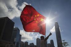 """Una persona con la bandera de China, levanta su dedo pulgar en apoyo al gobierno, durante una manifestación afuera del Consejo Legislativo, en Hong Kong, China, 17 de junio de 2015. China intensificará la """"inversión efectiva"""" en sectores clave para apuntalar su desacelerada economía, dijo el miércoles el gabinete del país asiático. REUTERS/Tyrone Siu"""